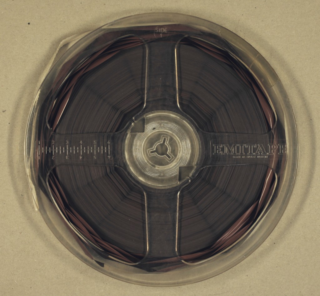A deteriorating reel of tape showing signs of 'spoking' (the tape shrinking and becoming tighter, pulling it taut around the centre of the reel, causing lines of tension to radiate out from the centre) and 'cupping' (the tape on the outer edges rolling in on itself)