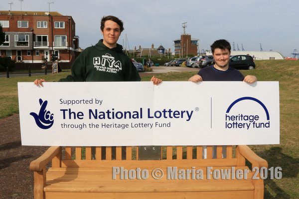 Photograph of Brandon and Stephen holding HLF sign behind listening bench