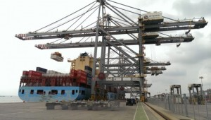 Photograph of cranes loading container ship
